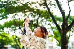 A estudante asiática aprende a fotografia com a câmera de bolso pequena exterior no dia Imagem de Stock