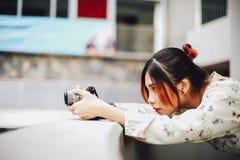 A estudante asiática aprende a fotografia com a câmera de bolso pequena exterior no dia Foto de Stock