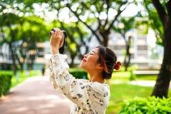 A estudante asiática aprende a fotografia com a câmera de bolso pequena exterior no dia Fotografia de Stock
