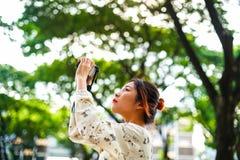A estudante asiática aprende a fotografia com a câmera de bolso pequena exterior no dia Imagens de Stock