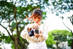 A estudante asiática aprende a fotografia com a câmera de bolso pequena exterior no dia Fotos de Stock Royalty Free