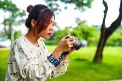 A estudante asiática aprende a fotografia com a câmera de bolso pequena exterior no dia Imagens de Stock Royalty Free
