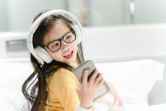 Estudante asiática feliz que escuta a música com fones de ouvido foto de stock