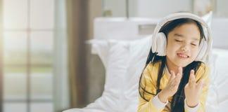 Estudante asiática feliz que escuta a música com fones de ouvido fotos de stock