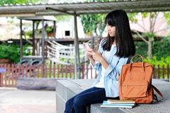 Estudante asiática nova que usa o telefone esperto ao sentar-se no terreno da escola, educação em linha, gen Z, uma comunicação d imagem de stock royalty free