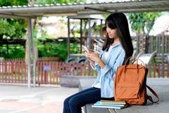 Estudante asiática nova que usa o telefone esperto ao sentar-se no terreno da escola, educação em linha, gen Z, uma comunicação d fotografia de stock
