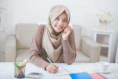 Estudante asiático fêmea bonito com o hijab que faz trabalhos de casa imagens de stock royalty free