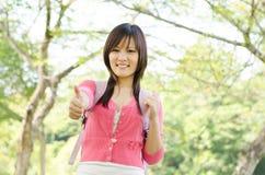 Estudante asiático novo da universitária que mostra o polegar acima imagens de stock