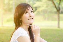 Estudante asiático novo da universitária que tem um pensamento imagens de stock royalty free