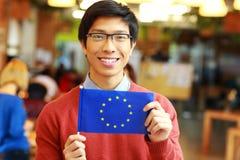Estudante asiático que guarda a bandeira da união de Europa Fotografia de Stock