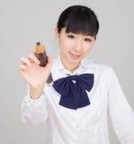 Estudante asiática na farda da escola que estuda com um lápis de tamanho grande Fotografia de Stock Royalty Free