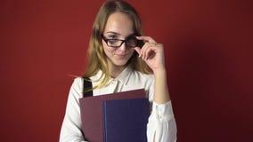 Estudante atrativo Blonde Girl com vidros no vermelho video estoque