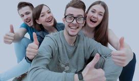 Estudante bem sucedido e seus amigos que sentam-se guardando um polegar acima do Fotografia de Stock