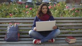 Estudante Biracial no humor elevado que senta-se no banco, sonhando sobre o futuro brilhante vídeos de arquivo