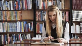 Estudante bonita que lê um livro na biblioteca video estoque