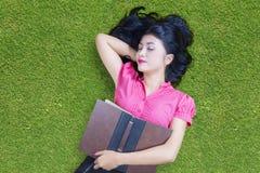 Estudante bonito com livro que dorme na grama Imagem de Stock