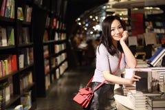 A estudante bonito consideravelmente nova bonita chinesa asiática Teenager da mulher leu o livro no sorriso da biblioteca da livr fotografia de stock royalty free