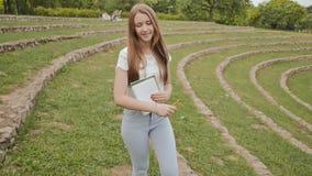 Estudante bonito da moça com livros de texto e dar uma volta de sorriso das notas através de um grande estádio verde Resto durant filme