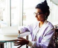 Estudante bonito nova do moderno que senta-se no café com o caderno com referência a foto de stock royalty free