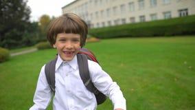 Estudante bonito pequena de sorriso do menino com a trouxa que vai e que corre à escola fora, estudante de primeiro grau, prelimi video estoque