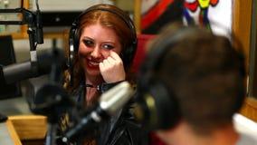 Estudante bonito que entrevista alguém para o rádio no estúdio filme
