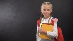 A estudante bonito que guarda livros com EUA minúsculos embandeira pronto para aprender a língua estrangeira filme