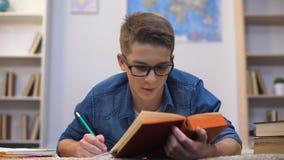 Estudante cansado nervoso do adolescente que faz os trabalhos de casa, sentindo esgotados, fim do prazo filme