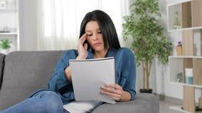 Estudante cansado que estuda notas da leitura em casa vídeos de arquivo
