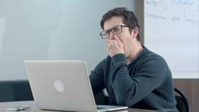 Estudante cansado que pensa sobre seu trabalho e que usa o portátil Imagens de Stock