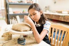 Estudante Carving Floral Pattern em Clay During Pottery Class fotografia de stock
