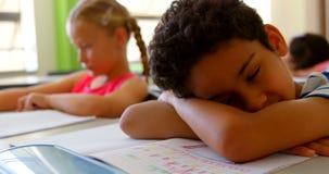 Estudante caucasiano que dorme na mesa na sala de aula na escola 4k filme