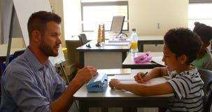 Estudante caucasiano que estuda com o professor primário masculino na sala de aula na escola 4k video estoque