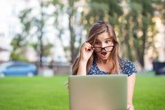 Estudante chocado com o laptop que olha o PC que guarda vidros para baixo em choque foto de stock