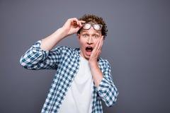 Estudante chocado encaracolado-de cabelo considerável do homem novo do wow, levantando o gl fotografia de stock