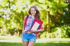 Estudante com livros e dobradores no terreno Imagens de Stock Royalty Free