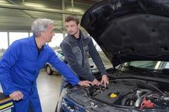 Estudante com o instrutor que repara o carro durante a aprendizagem Fotografia de Stock
