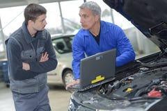 Estudante com o instrutor que repara o carro durante a aprendizagem Foto de Stock Royalty Free
