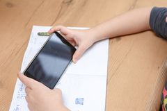 Estudante com o smartphone que faz trabalhos de casa em casa Fotografia de Stock Royalty Free