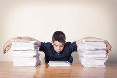 Estudante com os papéis empilhados imagem de stock