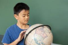 Estudante com posição do globo contra o quadro verde em uma sala de aula imagens de stock royalty free