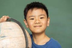 Estudante com posição do globo contra o quadro verde em uma sala de aula imagens de stock
