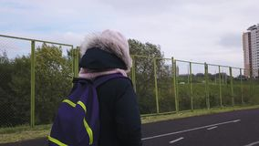 A estudante com trouxa atravessa à escola o estádio em um dia frio do outono vídeos de arquivo