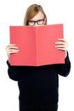 Estudante com uma aprendizagem de livro vermelha atenta Fotos de Stock Royalty Free