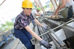 Estudante consideravelmente fêmea que faz o trabalho prático na fábrica foto de stock