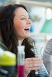 Estudante consideravelmente fêmea que ri ao misturar reagentes imagem de stock royalty free