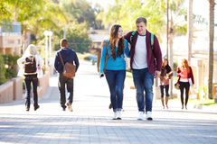 Estudante Couple Walking Outdoors no campus universitário fotos de stock royalty free
