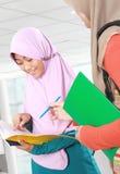 Estudante da criança dos muçulmanos que discute algo na biblioteca imagens de stock