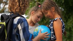 Estudante da escola primária com globo do mundo As crianças comunicam-se entusiasticamente De volta ? escola video estoque