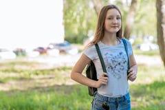 Estudante da menina verão na natureza Atrás dele uma trouxa Espaço livre para o texto acampar Sorrisos felizmente imagens de stock