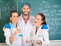Estudante da química do grupo com garrafa. imagem de stock